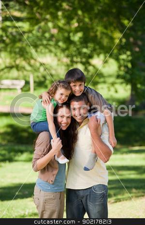 Parents giving children a piggyback stock photo, Parents giving children a piggyback by Wavebreak Media