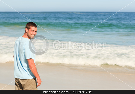 Handsome man walking on the beach stock photo, Handsome man walking on the beach by Wavebreak Media
