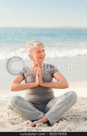 Senior woman practicing yoga on the beach stock photo, Senior woman practicing yoga on the beach by Wavebreak Media