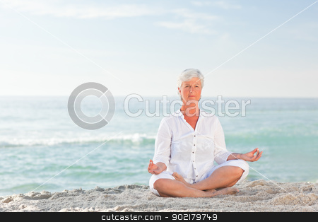Mature woman practicing yoga on the beach stock photo, Mature woman practicing yoga on the beach by Wavebreak Media