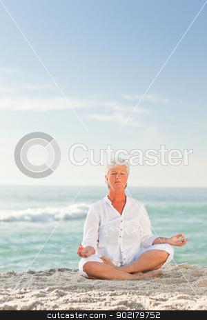 Mature woman practicing yoga on the beach stock photo, Mature woman practicing yoga on the beach by Wavebreak Media
