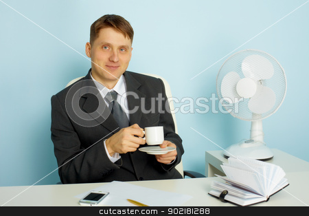 Attractive young man with a cup of coffee stock photo, Attractive smiling young man with a cup of coffee in the office  by Alexey Romanov