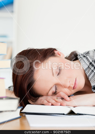 Beautiful red-haired girl having a rest while studying for an ex stock photo, Beautiful red-haired girl having a rest while studying for an examination at her desk by Wavebreak Media