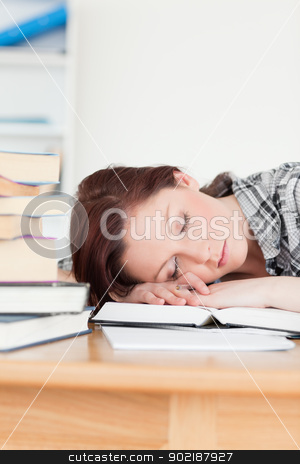 Attractive red-haired girl having a rest while studying for an e stock photo, Attractive red-haired girl having a rest while studying for an examination at her desk by Wavebreak Media