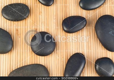 Black stones against bamboo background stock photo, Black stones against a bamboo background by Wavebreak Media