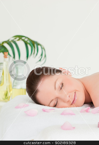 Portrait of a young woman lying on a massage table with petals stock photo, Portrait of a young woman lying on a massage table with petals by Wavebreak Media