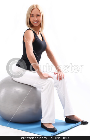Happy woman sitting on a fitness ball stock photo, Close up of happy and beautiful woman sitting on a fitness ball isolated on a white by yekostock