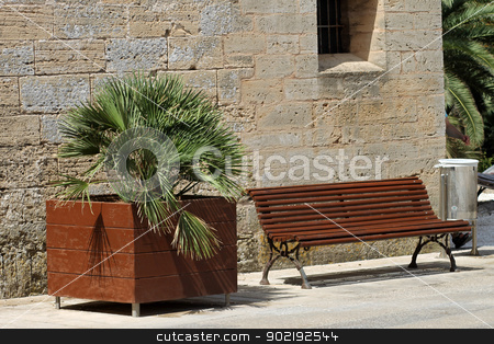Vacant wooden park bench stock photo, Vacant wooden park bench with old building in background by Martin Crowdy
