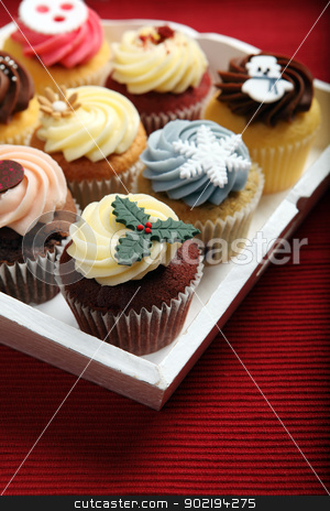 Holiday cupcakes stock photo, Photo of many cupcakes decorated for Christmas on a white tray. Focus on closest cupcake. by © Ron Sumners