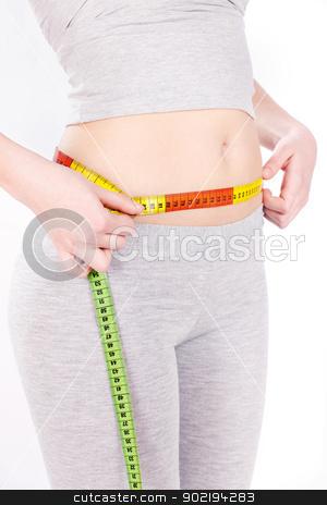 Measure tape around woman's waist stock photo, Measure tape around slim woman's waist by iMarin