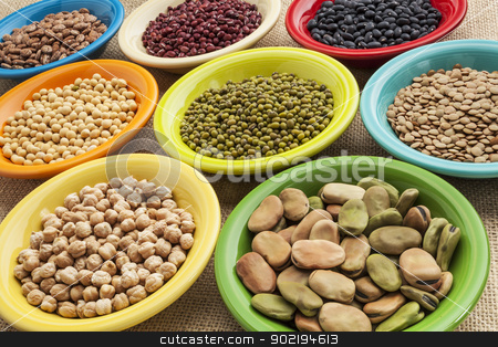 beans in bowls abstract stock photo, variety of legumes (fava bean, mung bean, soy, green lentils, adzuki, black, pinto, chickpea) in colorful ceramic bowls on canvas by Marek Uliasz
