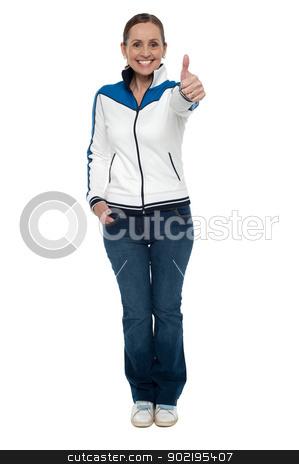 Casual charming woman gesturing thumbs up stock photo, Casual charming woman gesturing thumbs up. Full length studio shot. by Ishay Botbol