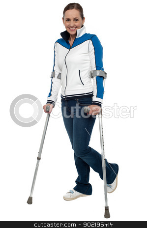 Woman walking with the support of crutches stock photo, Full length shot of a woman walking with the support of crutches. by Ishay Botbol