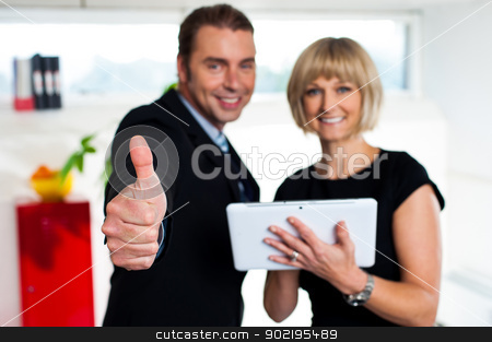 Secretary with a tablet posing with her successful boss stock photo, Our business is growing. Awesome team work. by Ishay Botbol