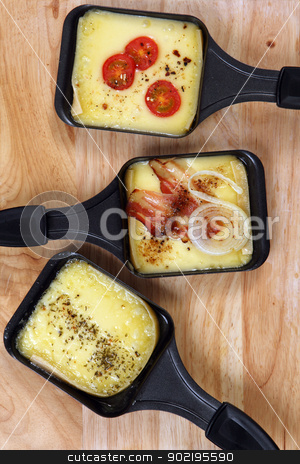 Raclette trays stock photo, Photo of a three Raclette trays with melted cheese, herbs, cherry tomato, bacon and onion. by © Ron Sumners