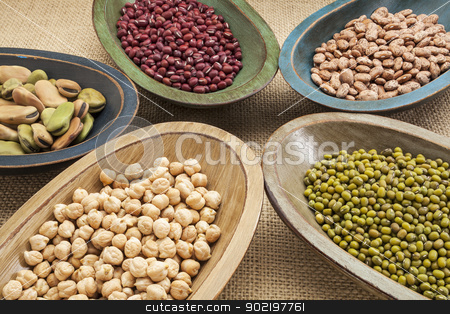 beans in bowls abstract stock photo, variety of legumes (fava bean, mung bean, adzuki, pinto, chickpea) in colorful rustic wood bowls on canvas by Marek Uliasz