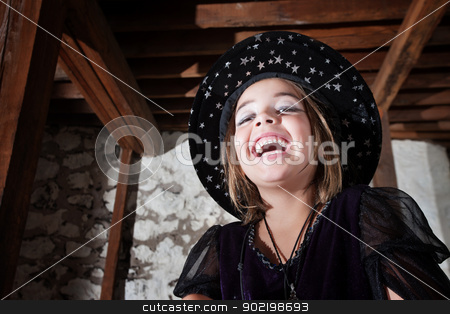 Cute Young WitchLaughing stock photo, Laughing European child dressed as a witch indoors by Scott Griessel