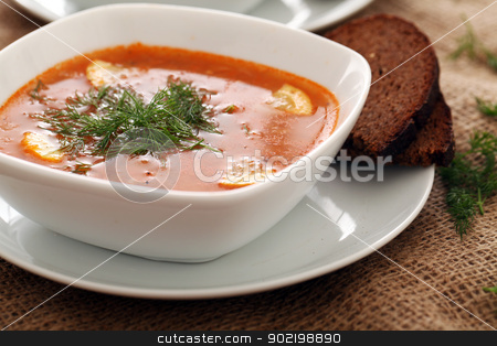 Image of bowls of hot red soup served with bread stock photo, Image of bowls of hot red soup served with bread on a beige tablecloth by yekostock