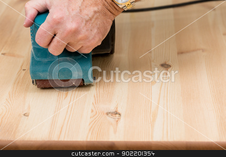 Mans hand on belt sander on pine wood stock photo, Man holding a belt sander on pine floor or table sanding surface by Steven Heap