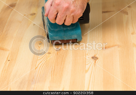 Mans hand on belt sander on pine wood stock photo, Man holding a belt sander on pine floor or table sanding surface by Steven Heap