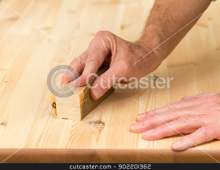 Mans hand on sanding block on pine wood stock photo, Man holding sanding block on pine floor or table sanding surface by Steven Heap