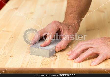 Mans hand on sanding block on pine wood stock photo, Man holding sanding block on pine floor or table sanding surface by Steven Heap