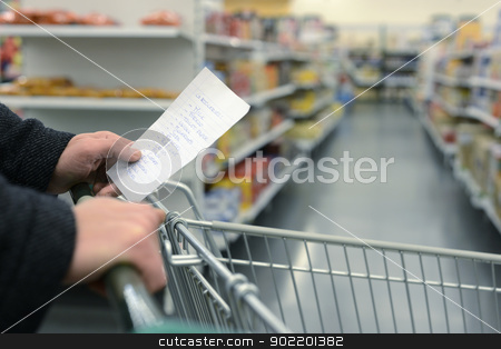 Supermarket shopping cart stock photo, Hand pushing a shopping cart through the aisles of a supermarket, holding a list with groceries, with the daily necessities in handwriting on a slip of paper by Corepics VOF