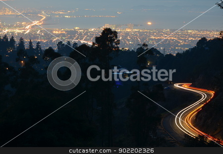 Light Trails Above San Francisco Bay stock photo, Cars ascend and descend Skyline Blvd. looking over the San Francisco Bay. Cars enter and exit the city on the Bay Bridge in the upper left corner. In the distance you can see the lights of Alcatraz, Treasure and Yerba Buena Islands, and the Golden Gate Bridge. Taken off Grizzly Peak Blvd. by Avalon