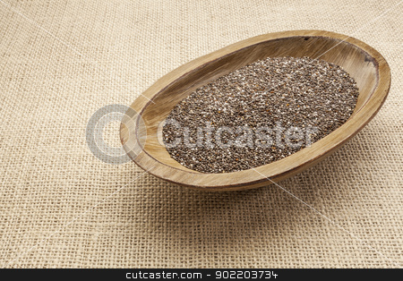chia seeds in bowl stock photo, chia seeds in a rustic oval wood bowl against canvas by Marek Uliasz