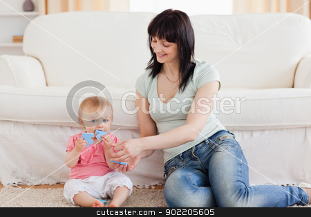 Attractive woman holding her baby in her arms while sitting on a stock photo, Attractive woman holding her baby in her arms while sitting on a carpet in the living room by Wavebreak Media