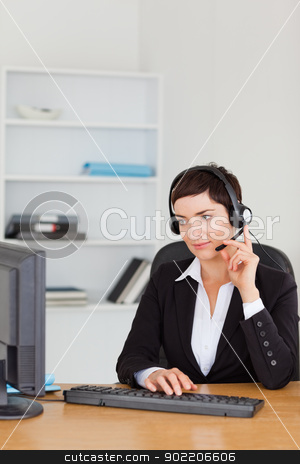 Portrait of a secretary calling with a headset stock photo, Portrait of a secretary calling with a headset in her office by Wavebreak Media