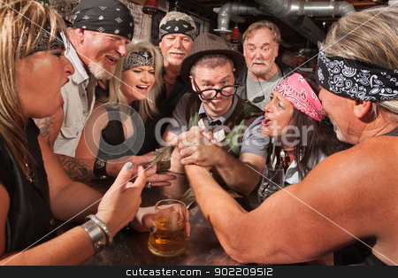 Nerd Wins Arm Wrestling Match stock photo, Confident nerd wins arm wrestling match in biker bar by Scott Griessel
