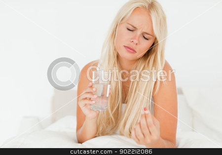 Woman taking a pill stock photo, Woman taking a pill in her bedroom by Wavebreak Media