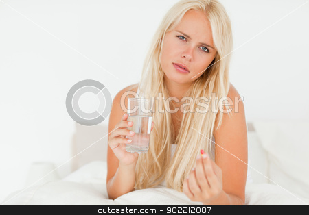 Blonde woman taking a pill stock photo, Blonde woman taking a pill in her bedroom by Wavebreak Media