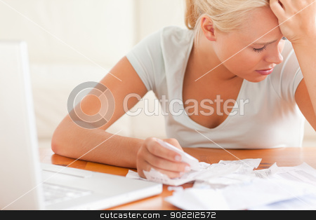 Sad blond woman accounting stock photo, Sad blond woman accounting in the living room by Wavebreak Media