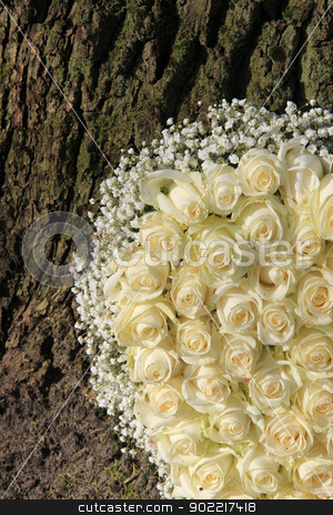 Detail of white floral arramgement near a tree stock photo, Detail of a white floral arrangement with white roses near a tree by Porto Sabbia
