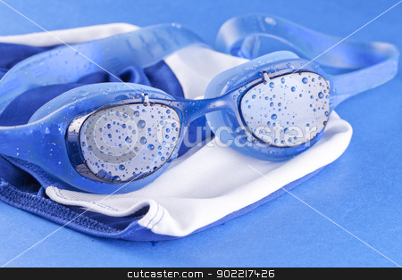 Swimming goggles stock photo, A pair of swimming goggles over blue, with earplugs by Fabio Alcini