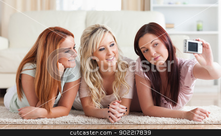 Cute women lying on the floor taking a picture stock photo, Cute women lying on the floor taking a picture in a living room by Wavebreak Media