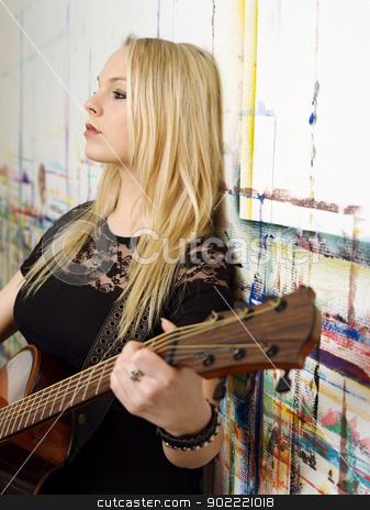 Young blond playing guitar stock photo, Photo of a young blond female holding an acoustic guitar and leaning up against a wall. by © Ron Sumners