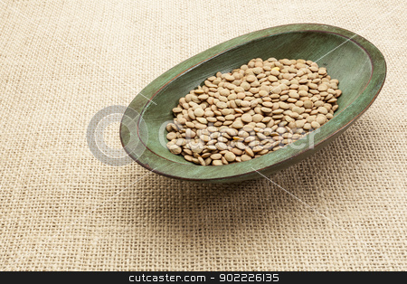 green lentils stock photo, green lentils in a rustic wood bowl against burlap canvas by Marek Uliasz