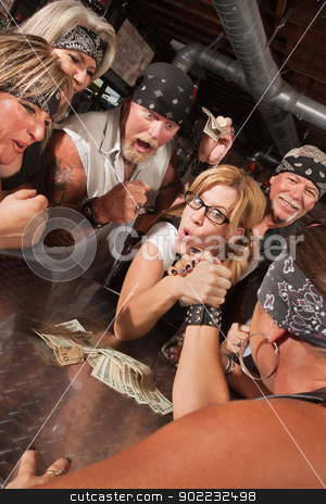 Female Nerd Arm Wrestling with Biker stock photo, Excited motorcycle gang betting on arm wrestling match with nerd by Scott Griessel