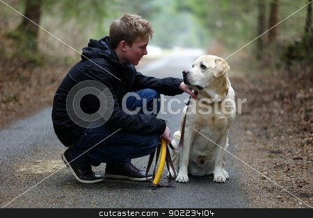 Young boy with dog stock photo, Young boy with his labrador in the forest by Michael Jenewein