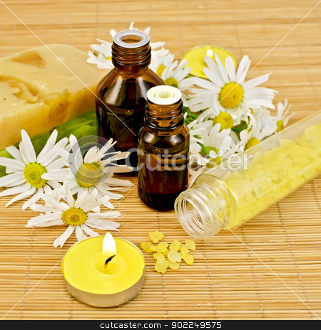 Oil yellow with soap and candles stock photo, Oil in two different bottles, two homemade soap, bath salt, two candles with flames and chamomile flowers on a bamboo mat by rezkrr