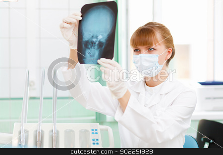 Female doctor with X-ray stock photo, Young female doctor holding a X-ray sheet by Sergey Nivens
