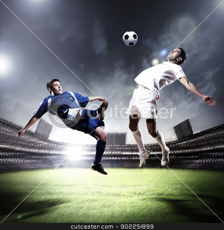 two football players striking the ball stock photo, two football players in jump to strike the ball at the stadium by Sergey Nivens