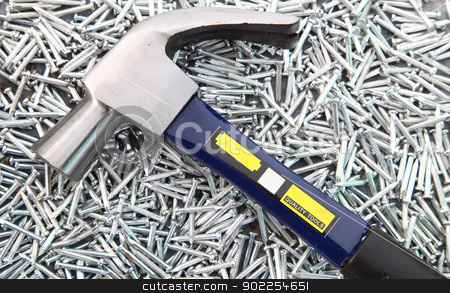 Hammer on Nails stock photo, Hammer on heap of  Silver Concrete nails by Vichaya Kiatying-Angsulee