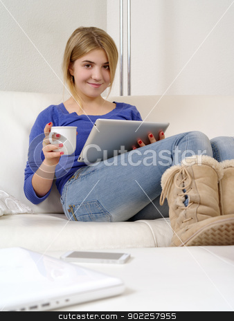 Pretty teenager using a digital tablet stock photo, Photo of a happy young teenage female using a computer tablet at home.  by © Ron Sumners