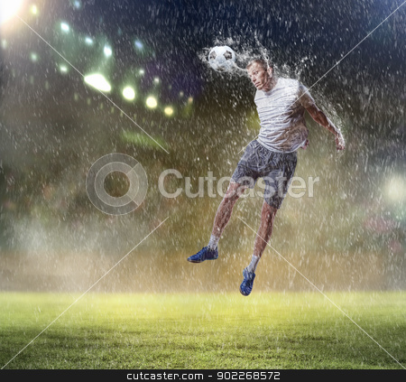 football player striking the ball stock photo, football player in white shirt striking the ball with head at the stadium under the rain by Sergey Nivens
