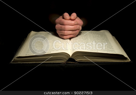 hands on biblie stock photo, A mans hands clasped in prayer over a  Bible by Vitaliy Pakhnyushchyy