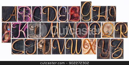 alphabet in ornamental wood type stock photo, complete English alphabet  in ornamental script wood type - a  collage of 26 isolated letterpress printing blocks stained by color and black ink by Marek Uliasz